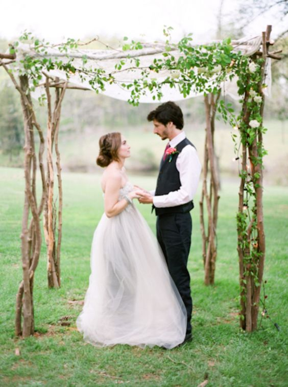 branch wedding chuppah decorated with floiage and flowy fabric