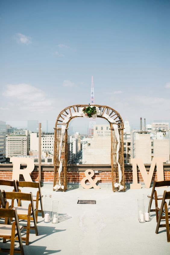 industrial wedding ceremony space with a wooden and fabric arbor