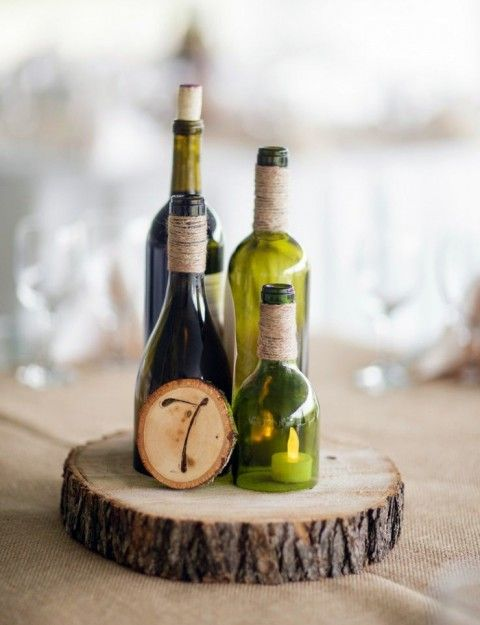 wine bottles, a cut wine bottle candle holder and a wood slice table number