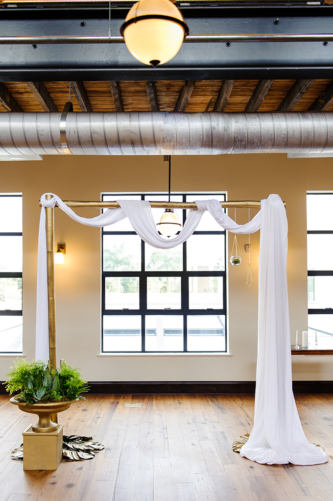 The wedding arch was decorated with fabric and hanging pots