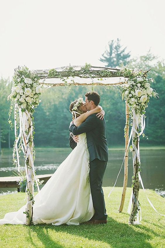 birch wedding arch decorated with ribbon and lush flowers