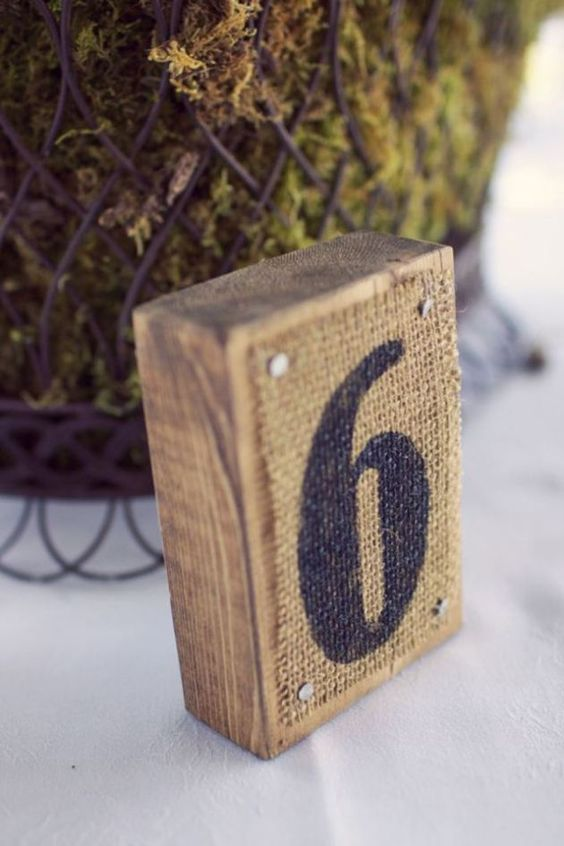 wood pieces with table numbers on burlap