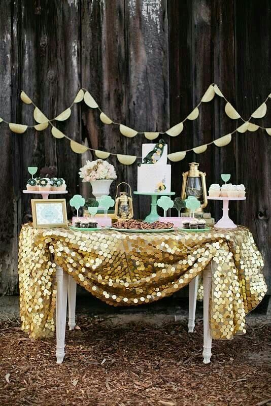 cover the dessert table with a large gold sequin tablecloth and place mint cake and cupcake stands