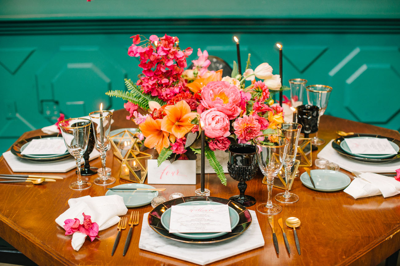 Black glasses, gilded tableware, geometric candle holders and super bold flowers comprised a cool table setting