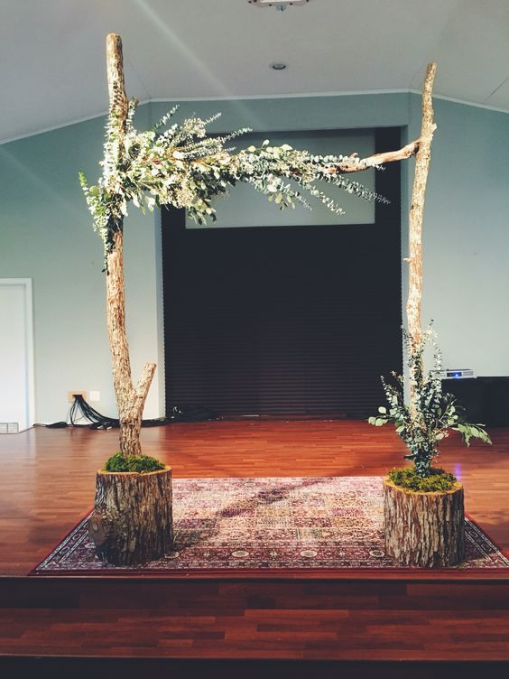 rough branches and logs arch with greenery
