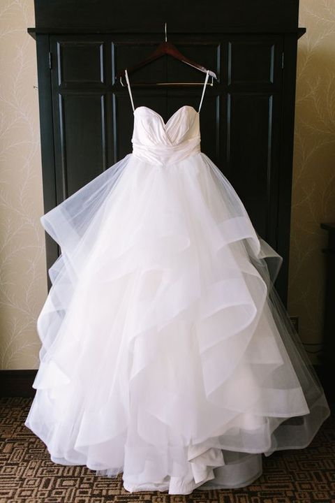 Picture Of Wedding Gown Hanging In A Contrasting Backdrop