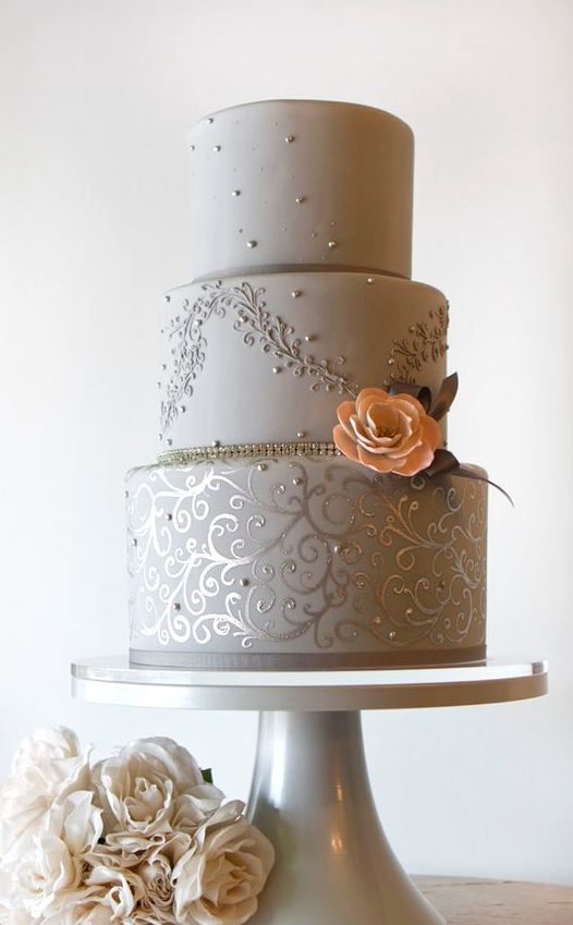 grey and silver wedding cake with a peach flower