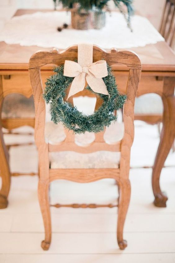 small fir wreath with beige ribbon looks awesome in vintage wooden chairs