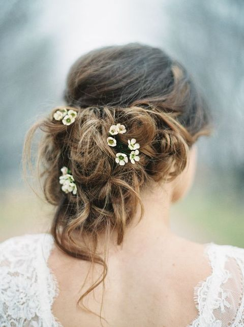 very messy updo with tiny fresh flowers tucked in