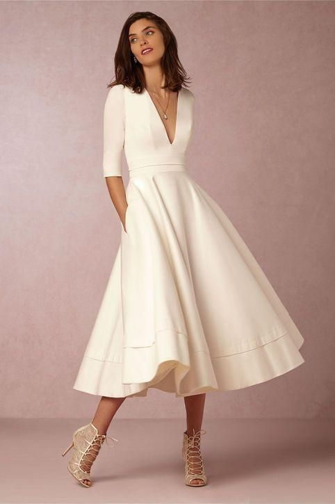 a calf length dress with a deep v neck and sleeves that go to