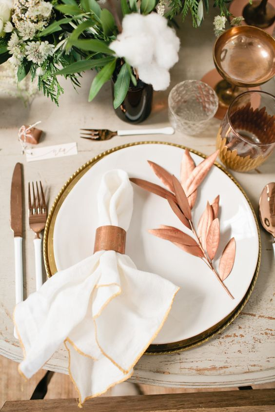 copper and cotton table setting with greenery
