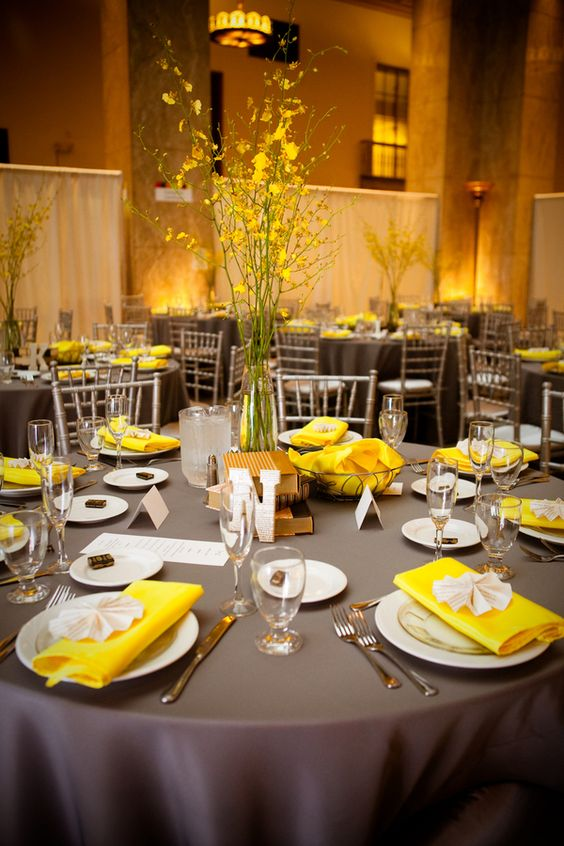 dark grey tablecloth with yellow napkins and a floral centerpiece