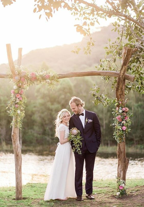 rough wood wedding arch decorated with flowers and greenery