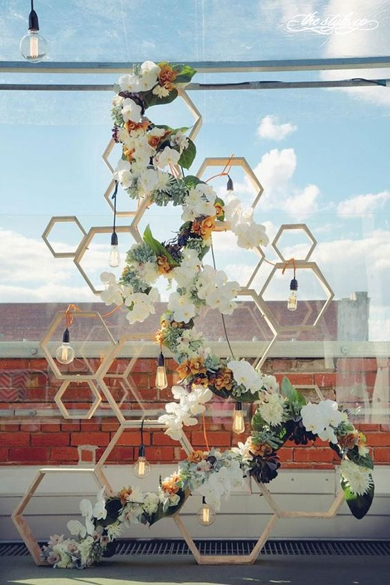 chic industrial and modern geometric wedding backdrop of wooden hexagons, bulbs and flowers