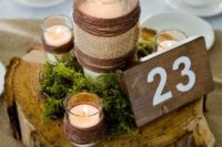 17 wood slice centerpiece with moss and candles and table numbers on a wood piece