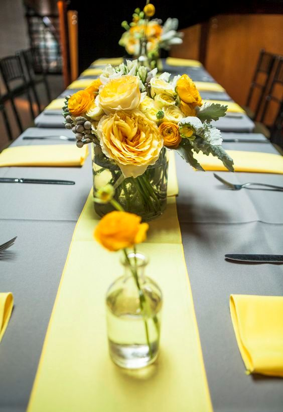 dove grey tablecloth, a yellow table runner and yellow floral centerpieces