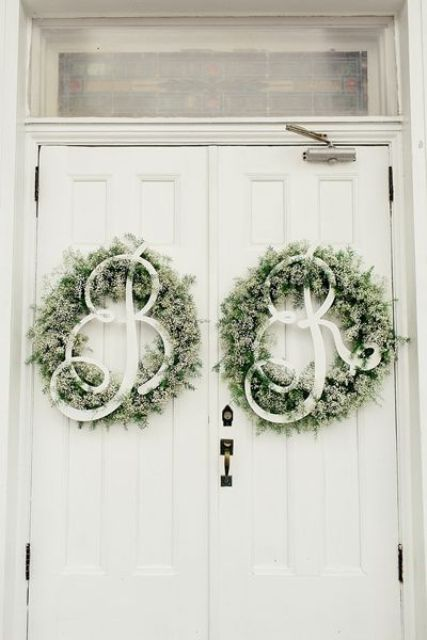evergreen wreaths with monograms of the couple