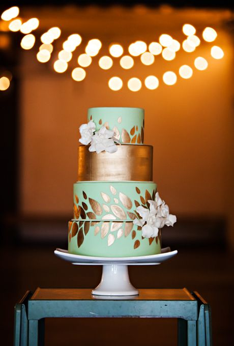 four-tiered mint-and-gold wedding cake with gold-leaf details and fresh flowers