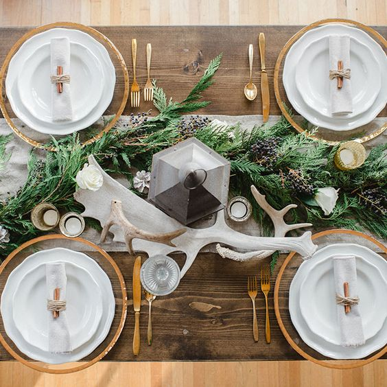 table runner made of fresh, seasonal greenery is a chic way to decorate tables at your winter reception