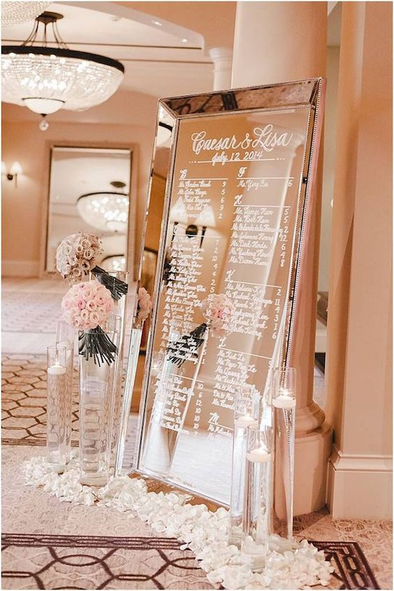 oversized mirror seating chart surrounded with flowers and petals