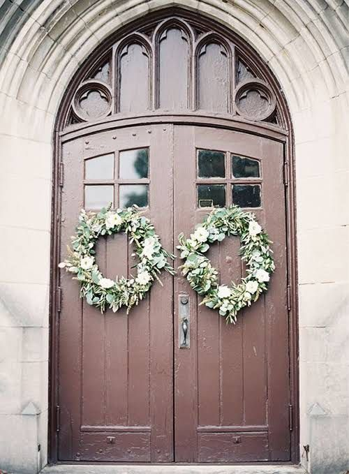 winter wedding wreaths with flowers on the venue doors