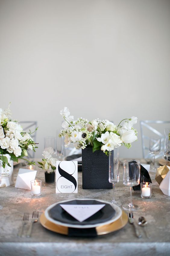 modern table setting with geometric details, candles and white flowers