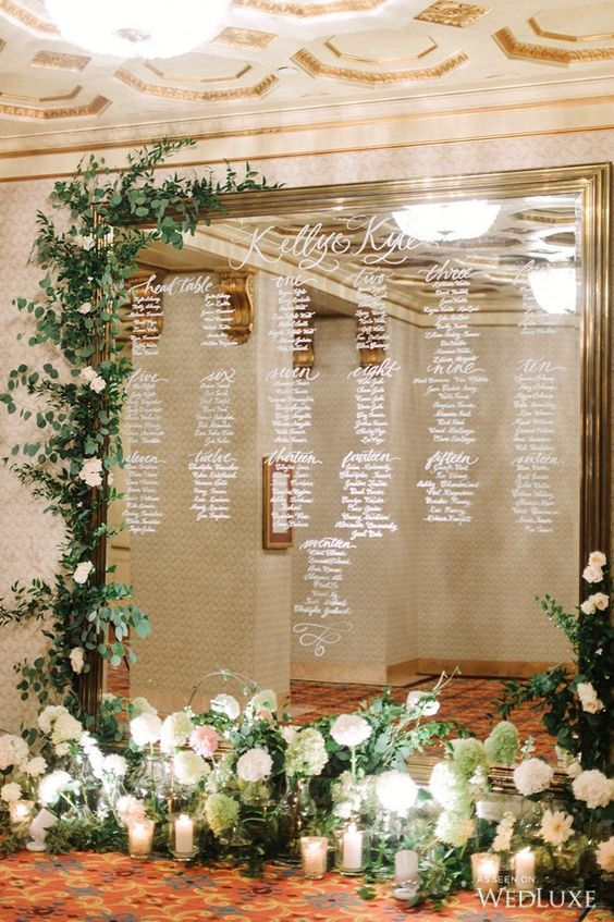 oversized seating chart decorated with candles and fresh flowers