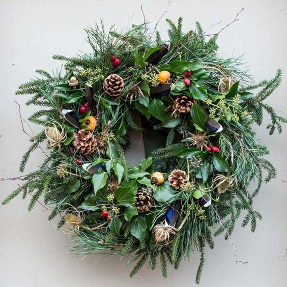 bold winter wedding wreath with pinecones, whistles and berries