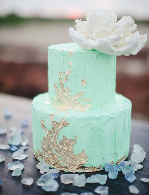 mint wedding cake with gold leaf and a large flower