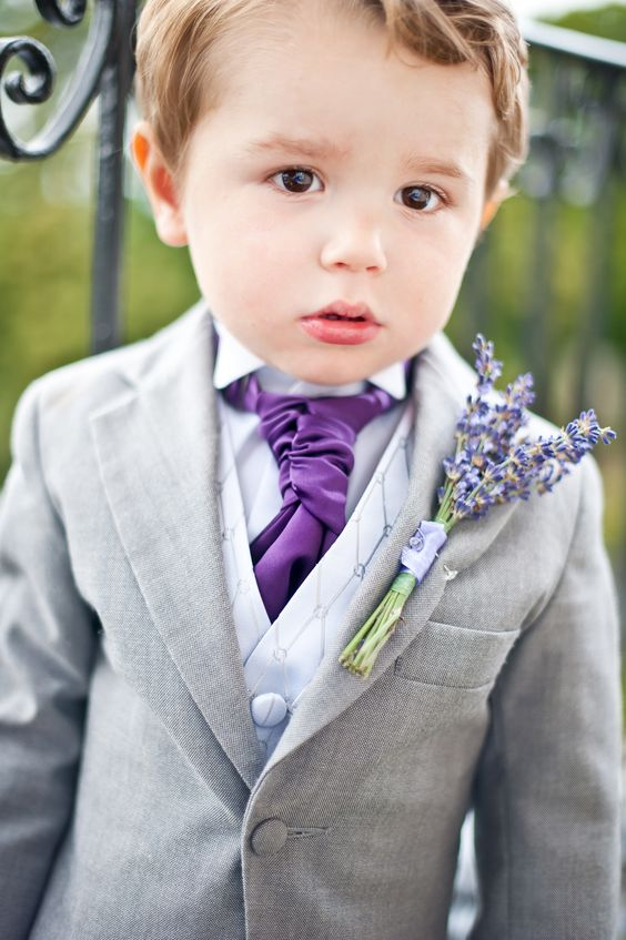 ringbearer in a light grey suit with a purple tie and a lavender boutonniere