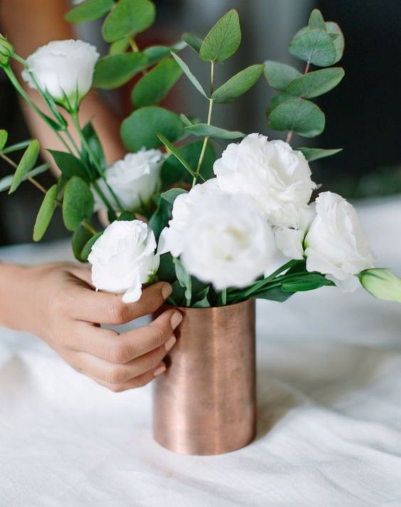 copper vase with white flowers and greenery for a centerpiece