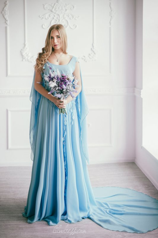 flowy and airy blue wedding dress with a train and a cape