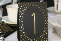 23 gold and black tented table cards with numbers