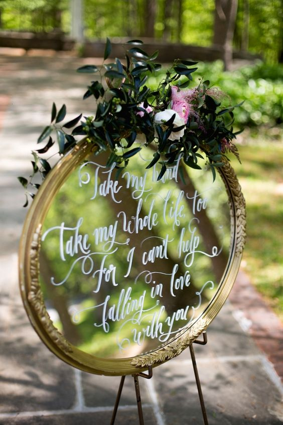 round mirror sign with greenery and flowers