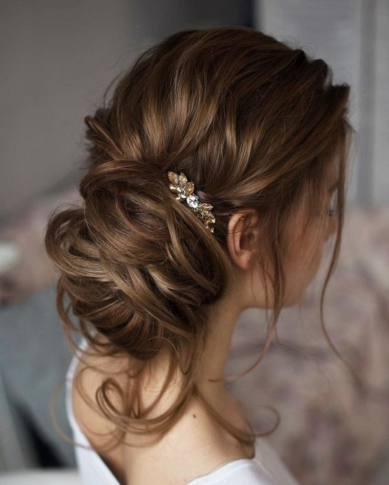 messy updo with a small crystal accessory for an accent