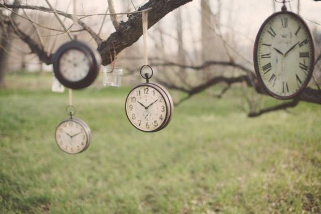 hanging vintage clocks from trees for outdoor decor