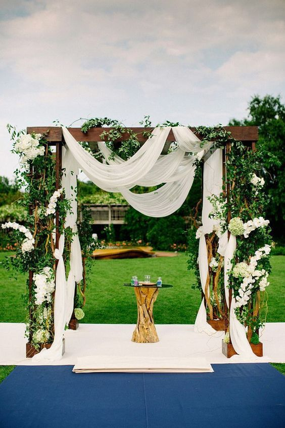 lush arch with white fabric and a lot of flowers and greenery