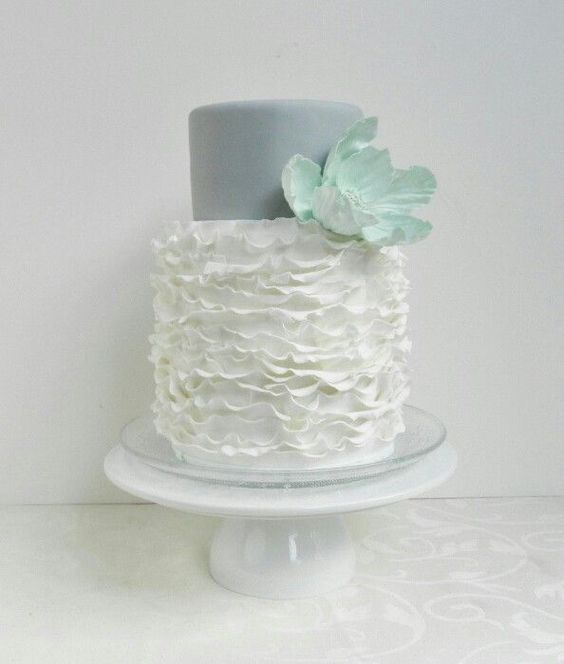 grey and ruffle ivory cake with a large mint flower