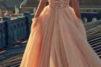 27 all-glam look in a ballerina ball gown with a full blush organza skirt, cathedral train, and a plunging bodice encrusted in sequins and pearls