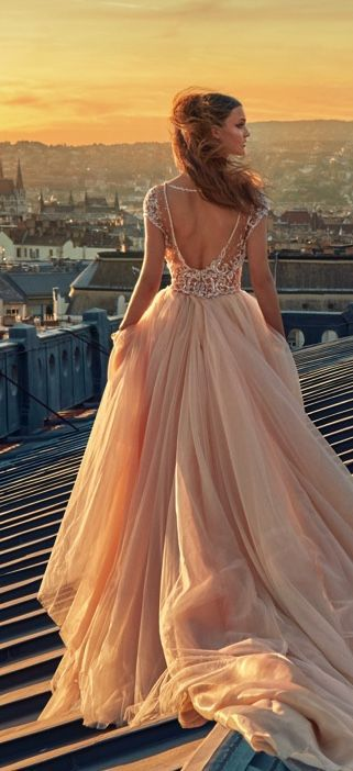 all-glam look in a ballerina ball gown with a full blush organza skirt, cathedral train, and a plunging bodice encrusted in sequins and pearls
