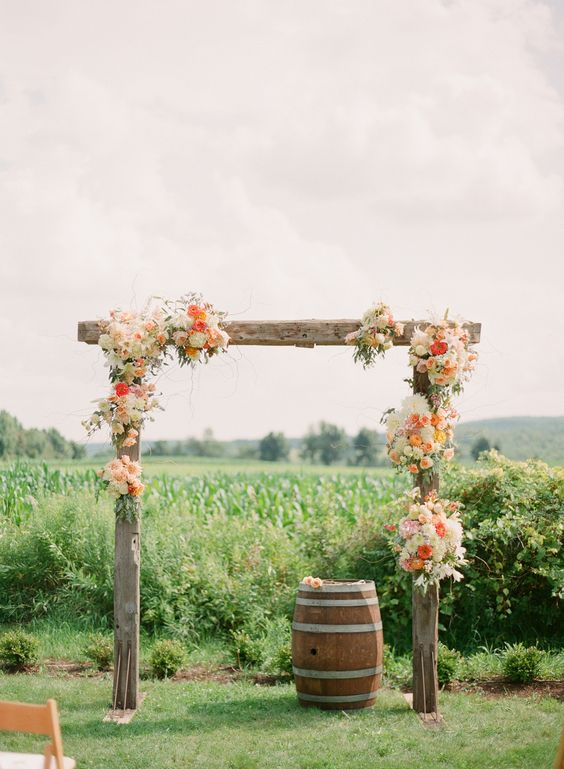rough wood wedding arch topped with flowers