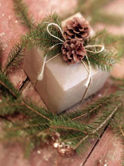 craft paper boxes tied up with string and adorned with evergreen branches and pine cones are perfect for a rustic winter wedding favor