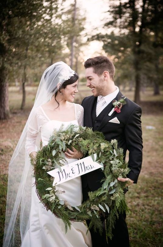 evergreen winter wedding wreath with a small sign