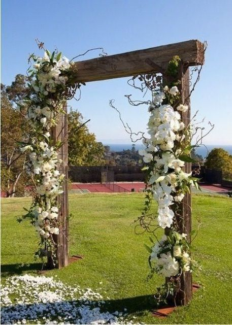 Picture of rustic wooden wedding arch decorated with white flowers junglespirit