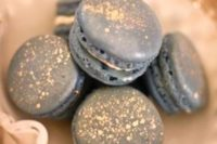 31 dark grey macarons with gold sprinkles