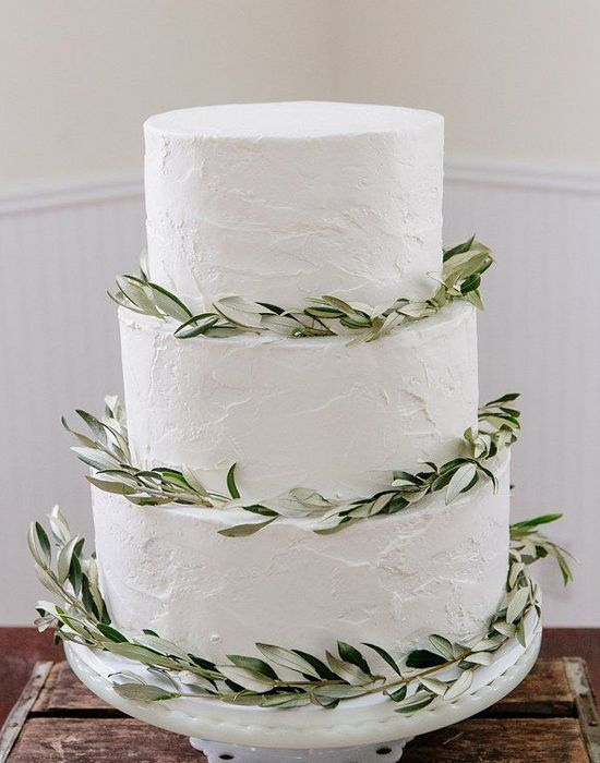 three-tier wedding cake decorated with greenery