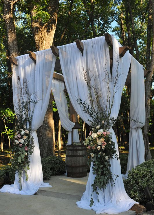 wedding pergola with white curtains and lush florals