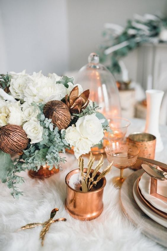 winter table setting with a fur tablecloth and copper and white touches