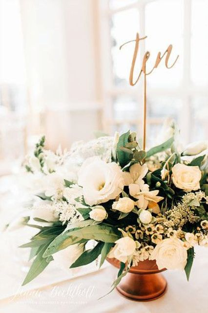 vintage copper vase with lush florals and a table number on a stick