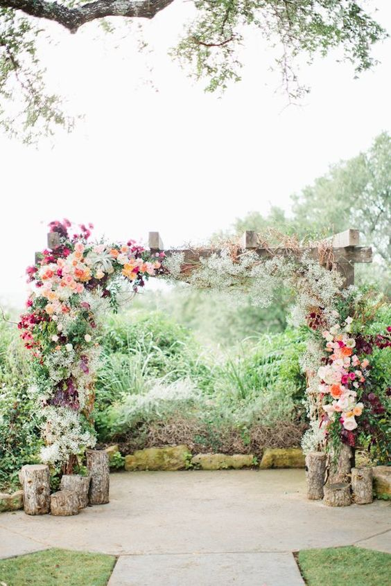 wooden arbor covered with lush bold flowers and with logs by its side